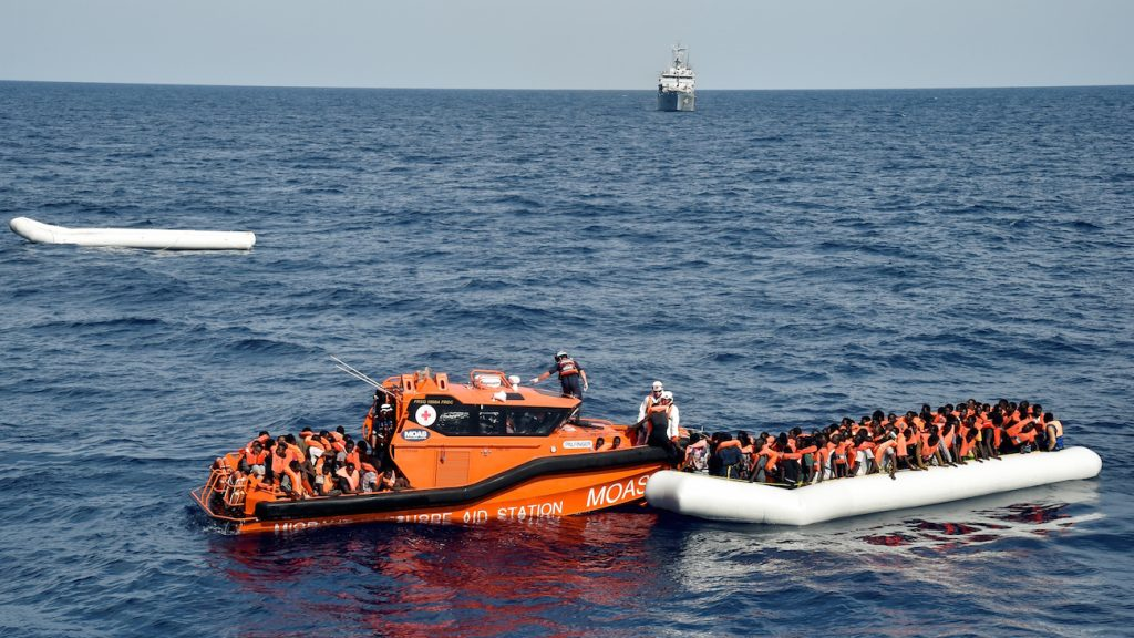"""Migrants and refugees on a rubber boat wait to be evacuated during a rescue operation by the crew of the Topaz Responder, a rescue ship run by Maltese NGO """"Moas"""" and the Italian Red Cross, on November 5, 2016 off the coast of Libya. / AFP PHOTO / ANDREAS SOLARO"""