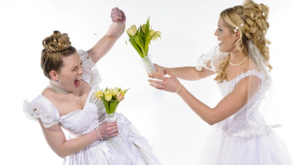 Two young brides in white wedding dresses fight against each other and beat with flowers
