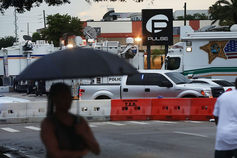 ORLANDO, FL - JUNE 18: People look out at the Pulse nightclub which is still an active crime scene on June 18, 2016 in Orlando, Florida. In what is being called the worst mass shooting in American history, Omar Mir Seddique Mateen killed 49 people at the popular gay nightclub early last Sunday. Fifty-three people were wounded in the attack which authorities and community leaders are still trying to come to terms with. (Photo by Spencer Platt/Getty Images)