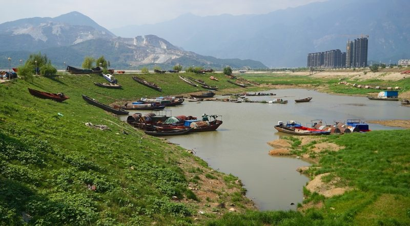 (161011) -- NANCHANG, Oct. 11, 2016 (Xinhua) -- Fishing boats are seen on the exposed bed of Poyang Lake in Lushan City, east China's Jiangxi Province, Oct. 10, 2016. China's largest freshwater lake, Poyang Lake, has seen dramatically decreasing water level in recent days. The lake hit low-water levels about 54 days earlier than average in previous years, according to statistics by the Jiangxi provincial hydrographic bureau.    (Xinhua/Hu Chenhuan) (wf)