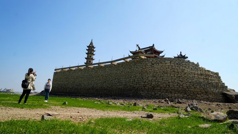 (161011) -- NANCHANG, Oct. 11, 2016 (Xinhua) -- Tourists visit an ancient architecture on the exposed bed of the Poyang Lake in Lushan City, east China's Jiangxi Province, Oct. 10, 2016. China's largest freshwater lake, Poyang Lake, has seen dramatically decreasing water level in recent days. The lake hit low-water levels about 54 days earlier than average in previous years, according to statistics by the Jiangxi provincial hydrographic bureau.    (Xinhua/Hu Chenhuan) (wf)