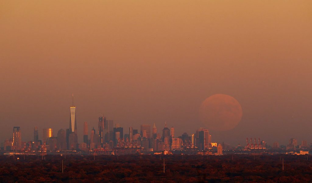 WATCHUNG, NJ - NOVEMBER 13: A super moon rises at sunset over lower Manhattan in New York City on November 13, 2016 as seen from Watchung, NJ. (Photo by Gary Hershorn/Getty Images)