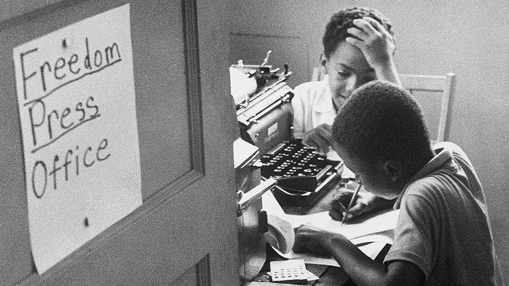 Two African American boys work in the Freedom Press Office in Hattiesburg, Mississippi, for the Mississippi Project, a campaign to increase black voter registration in the South. (Photo by © Bettmann/CORBIS/Bettmann Archive)
