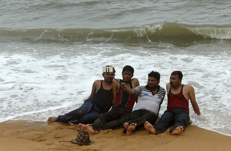 In this photograph taken on September 25, 2016, Indian tourists take a 'selfie' on Calangute Beach in GoaGoa has long attracted Western holidaymakers for its relaxed vibe, but rapid construction, swelling crowds and fears over safety are threatening the Indian state's global reputation as a tranquil haven. / AFP PHOTO / INDRANIL MUKHERJEE / TO GO WITH AFP STORY: India-Goa-tourism, FEATURE by  Peter Hutchison