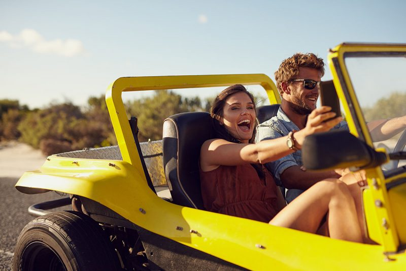 Excited happy couple enjoying road trip in their car. Man driving the car young woman taking a selfie from her mobile phone.