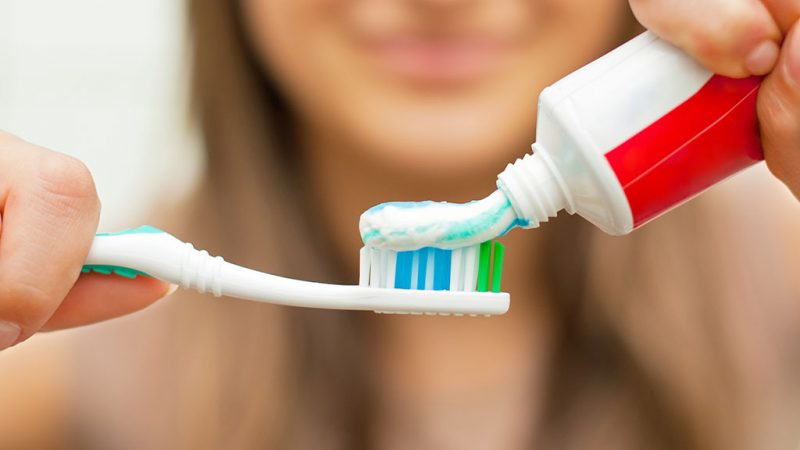 Young woman holding a toothbrush and placing toothpaste on it.