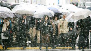 People walk on the street as snow is falling near the Shinjuku Station in Tokyo on Nov. 24, 2016. The snowfall at the metropolitan areas  in November was observed for the first time in 54 years. The Japan Meteorological Agency warned that a violent snowstorm is expected to hit the Kanto region. ( The Yomiuri Shimbun )