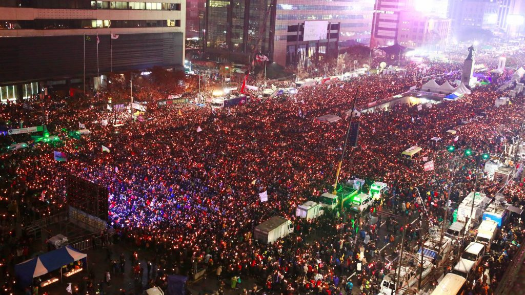 South Korean protesters take part in a candlelight procession towards the presidential house during a rally against South Korean President Park Geun-Hye in Seoul on November 26, 2016. Tens of thousands of protesters braved sleet and freezing temperatures in Seoul on November 26 to demand Park resign over a corruption scandal or face impeachment.   / AFP PHOTO / POOL / JEON HEON-KYUN
