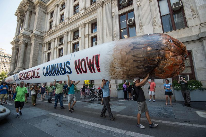 Supporters of former US Democratic presidential candidate Bernie Sanders hold a giant inflatable joint calling for the legalization of marijuana during a rally at City Hall in Philadelphia on July 25, 2016, as Democrats gather to formally annoint Hillary Clinton as their candidate for the November presidential election at the Democratic National Convention. / AFP PHOTO / NICHOLAS KAMM
