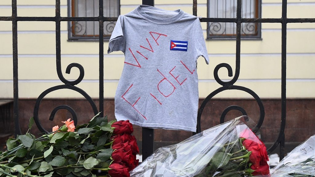 """Flowers, a t-shirt with an inscription reading """"Viva Fidel"""" and a cigar are left as a tribute to the late Cuban revolutionary leader Fidel Castro outside the country's embassy in Moscow on November 26, 2016. / AFP PHOTO / Vasily MAXIMOV"""