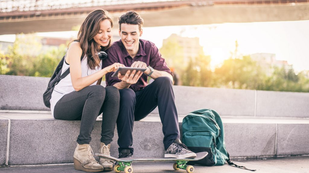 49080956 - beautiful couple sitting on a bench outdoors and looking at tablet - lovers having fun with new technology and shopping online