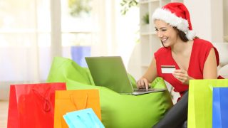 49296220 - fashion woman buying online for christmas sitting on the floor with colorful shopping bags at home