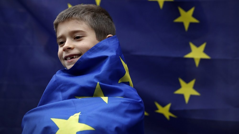 A young boy wrapped in a European Union (EU) flag stands outside The Royal Courts of Justice, Britain's High Court, in London on October 13, 2016, during a protest against the UK's decision to leave the EU. The battle over Britain's exit from the European Union (Brexit) reached the High Court on Thursday in a legal challenge to Prime Minister Theresa May's right to start negotiations for Britain to leave the EU without a vote in parliament. The move could delay Brexit if successful and set up an unprecedented constitutional face-off between the courts and the government. / AFP PHOTO / ADRIAN DENNIS
