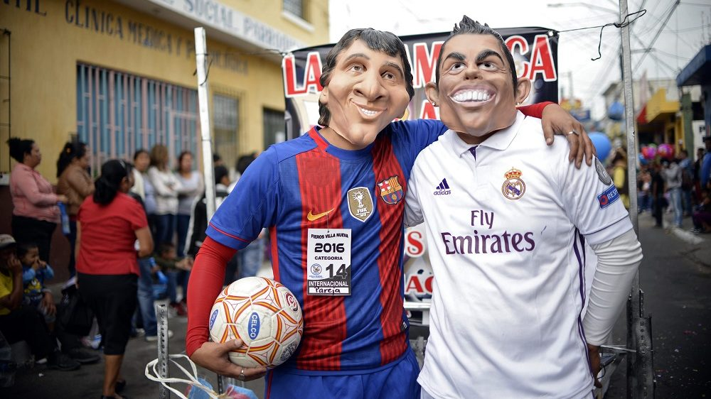 """Revellers disguised as Argentinian footballer Lionel Messi (L) of Spain's Barcelona and Portuguese Cristiano Ronaldo of Spain's Real Madrid take part in the traditional """"Convite de fieros"""" festival, as part of All Saints Day celebrations in Villa Nueva, 25 km south of Guatemala City, on November 1, 2016. / AFP PHOTO / JOHAN ORDONEZ"""