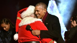 US President Barack Obama hugs and a man dressed as Santa Claus during the National Christmas Tree Lighting on the Ellipse of the National Mall in Washington on December 1, 2016.  / AFP PHOTO / Nicholas Kamm