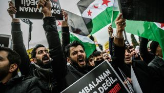 """Men hold placards and wave Syrian national flag as they chant slogans on December 2, 2016 in Istanbul during a demonstration to protest against the Syrian official regime and Russia's military operations in Aleppo.Elite Syrian troops moved into east Aleppo on December 1st, 2016 ahead of a push into the most densely populated areas, as regime ally Russia called for corridors to bring in aid and evacuate wounded. Despite global criticism including the UN warning Aleppo risked becoming a """"giant graveyard"""", government forces have pressed an assault to retake control of the divided city. / AFP PHOTO / OZAN KOSE"""