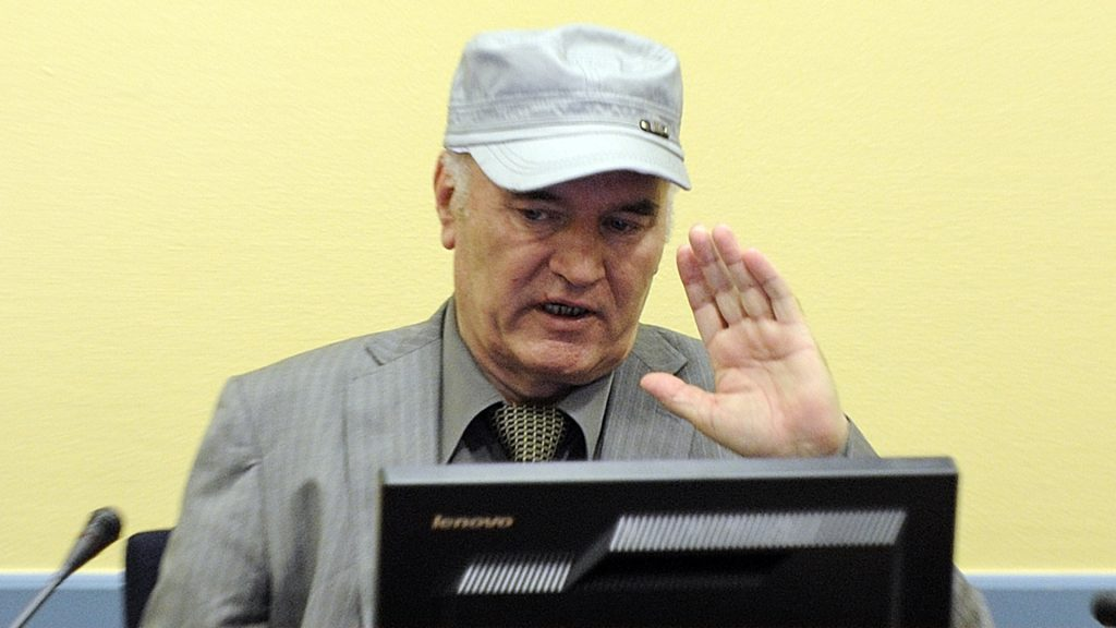 """(FILES) This file photo taken on June 3, 2011 at the UN Yugoslav war crimes tribunal in The Hague shows wartime Bosnian Serb General Ratko Mladic wearing a cap saluting in the court room at his initial appearance. Former feared Serb military commander Ratko Mladic, once dubbed """"The Butcher of Bosnia"""", is back in a UN court on December 5, 2016 as his trial for genocide and war crimes in the 1990s conflict nears an end, as prosecutors will begin three days of closing arguments and will likely call for a long jail term for genocide, as well as war crimes and crimes against humanity for his role in the bloody 1992-95 Bosnian conflict which saw Europe's worst bloodshed since World War II. / AFP PHOTO / POOL / MARTIN MEISSNER"""