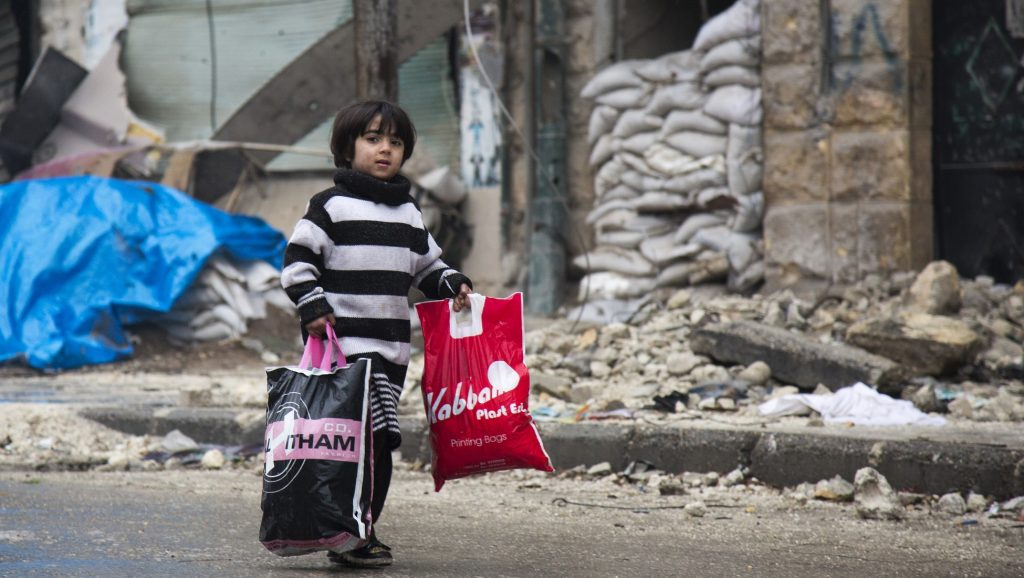 A Syrian boy is seen among other civilains leaving a rebel-held area of Aleppo towards the government-held side on December 13, 2016 during an operation by Syrian government forces to retake the embattled city. UN chief Ban Ki-moon expressed alarm over reports of atrocities against civilians Monday, as the battle for Aleppo entered its final phase with Syrian government forces on the verge of retaking rebel-held areas of the city.   / AFP PHOTO / KARAM AL-MASRI