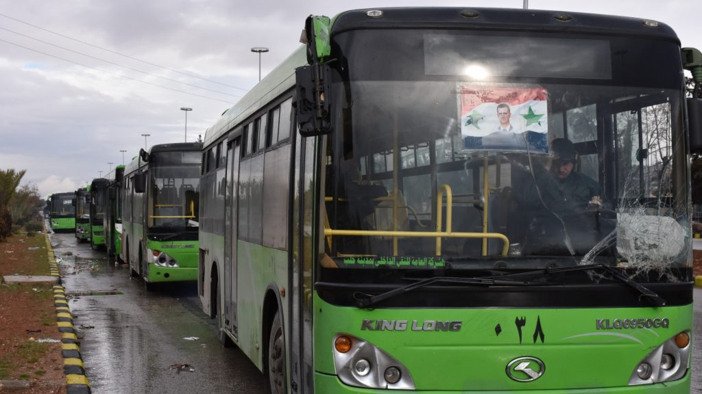 Buses which will be used to evacuate civilians leaving from rebel-held areas of Aleppo are seen waiting on December 14, 2016.  Thousands of cold and hungry civilians crowded the streets of Aleppo uncertain of their future after their planned evacuation from the last rebel pocket of the city was delayed.   / AFP PHOTO / George OURFALIAN