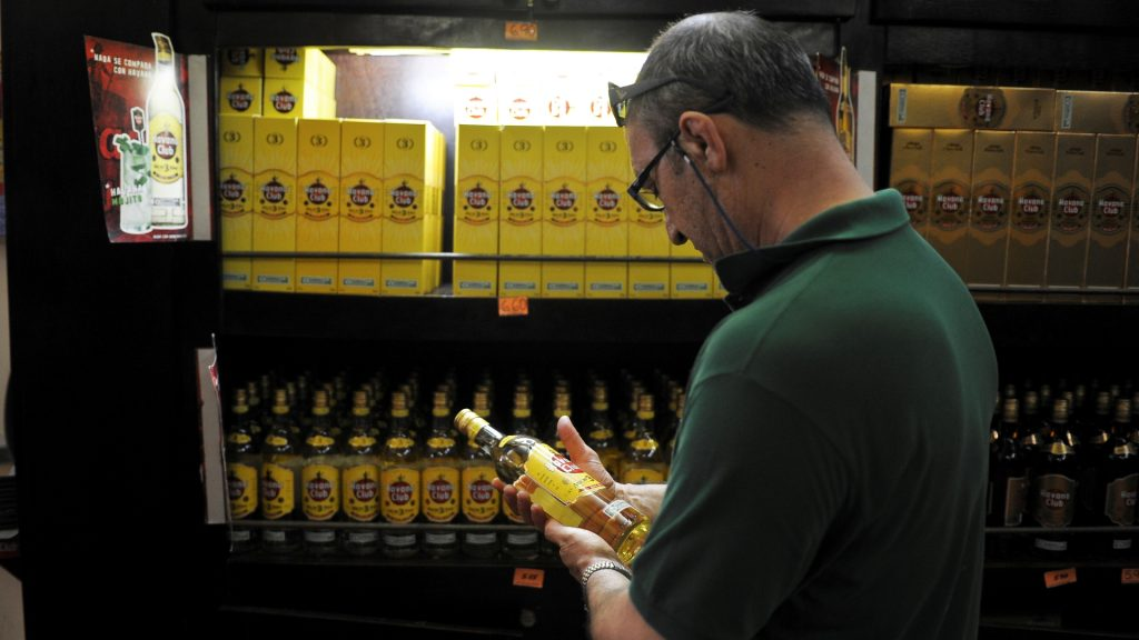 (FILES) This file photo taken on October 19, 2016 shows a tourist buying Cuban rum in a store of Havana, on October 18, 2016.  Cash-strapped Cuba has offered to pay its old debt to the Czech Republic with goods it can spare, including its coveted rum, the Czech finance ministry said on December 16, 2016.  / AFP PHOTO / YAMIL LAGE