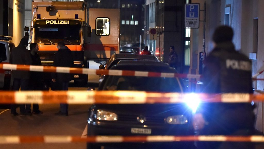 Swiss police are seen behind police cordon outside a Muslim prayer hall, central Zurich, on December 19, 2016, after three people were injured by gunfire. Local media reported the incident occurred in the Muslim prayer hall near the city's railway station. Swiss media said the three wounded people, all adults, were found in the street where the prayer hall is located. The suspected assailant had fled the scene and police sealed off the area.    / AFP PHOTO / MICHAEL BUHOLZER