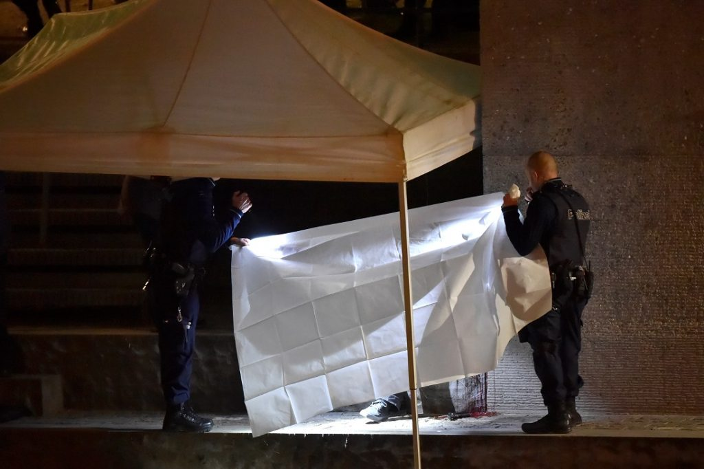 Swiss police officers hold a blanket to cover a dead body found near a Muslim prayer hall, central Zurich, on December 19, 2016, after three people were injured by gunfire. Local media reported the incident occurred in the Muslim prayer hall near the city's railway station. Swiss media said the three wounded people, all adults, were found in the street where the prayer hall is located. The suspected assailant had fled the scene and police sealed off the area. / AFP PHOTO / MICHAEL BUHOLZER