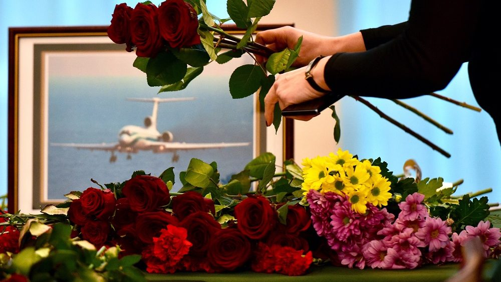 People lay flowers at the gate of the Russian embassy in Minsk, on December 26, 2016, a day after a military plane carrying 92 people, including dozens of members of the Red Army Choir, crashed in the Black Sea. The Russian defence ministry told agencies there was no sign of any survivors at the crash site and that 10 bodies had been recovered off the coast of the resort city of Sochi, as authorities pledged to dispatch an additional 100 divers to aid in the search.  / AFP PHOTO / MAXIM MALINOVSKY