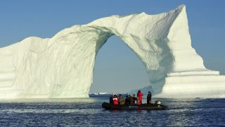 Denmark. Greenland. West coast. Zodiac near an arch shaped iceberg in the straight of Vaigat. 