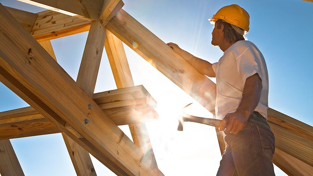 worker checking roof construction strong sun flare