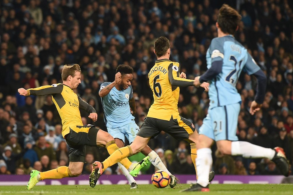 Manchester City's English midfielder Raheem Sterling (2nd L) shoots through players to score their second goal during the English Premier League football match between Manchester City and Arsenal at the Etihad Stadium in Manchester, north west England, on December 18, 2016. / AFP PHOTO / Paul ELLIS / RESTRICTED TO EDITORIAL USE. No use with unauthorized audio, video, data, fixture lists, club/league logos or 'live' services. Online in-match use limited to 75 images, no video emulation. No use in betting, games or single club/league/player publications.  /