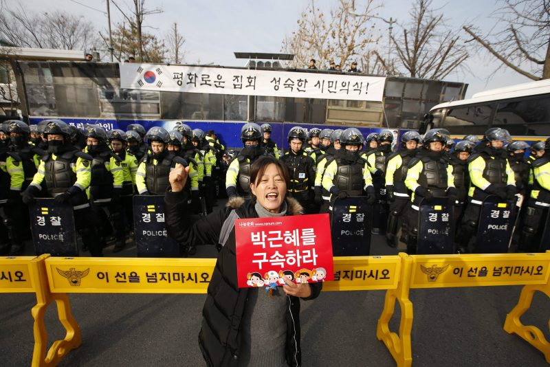 Szöul, 2016. december 3. Egy tüntetõ rendõrök sorfala elõtt követeli a korrupciós botrányba keveredett Pak Gun Hje dél-koreai elnök lemondását Szöulban 2016. december 3-án. (MTI/EPA/Dzson Hon Kjun)