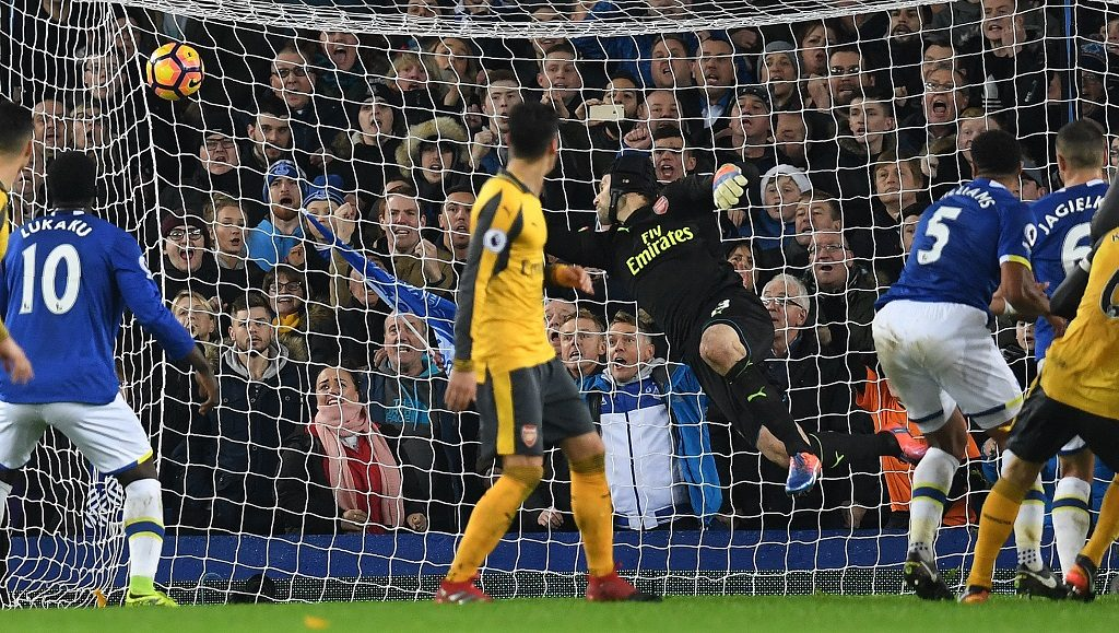 Everton's English-born Welsh defender Ashley Williams (2R) scores his team's second goal past Arsenal's Czech goalkeeper Petr Cech during the English Premier League football match between Everton and Arsenal at Goodison Park in Liverpool, north west England on December 13, 2016. Everton won the match 2-1. / AFP PHOTO / Paul ELLIS / RESTRICTED TO EDITORIAL USE. No use with unauthorized audio, video, data, fixture lists, club/league logos or 'live' services. Online in-match use limited to 75 images, no video emulation. No use in betting, games or single club/league/player publications.  /