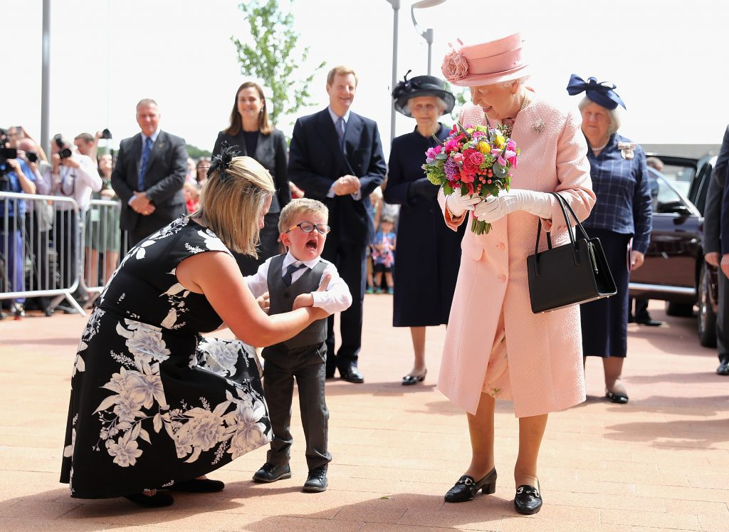 LIVERPOOL, ENGLAND - JUNE 22: Two year old Lewis Connet bursts into tears as he presents Queen Elizabeth II with flowers as she arrives with the Duke of Edinburgh to officially open Alderhey Children's Hospital during a visit to Liverpool on June 22, 2016 in Liverpool, England. (Photo by Chris Jackson-WPA Pool/Getty Images)
