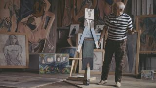 Spanish artist, sculptor and painter, Pablo Picasso (1881-1973) pictured smoking a cigarette as he examines one of his sculptures at his house near Cannes in France circa 1960. Versions of Picasso's painting Les Demoiselles d'Avignon can be seen along with other works on the wall behind the artist. (Photo by DGL/Paul Popper/Popperfoto/Getty Images)
