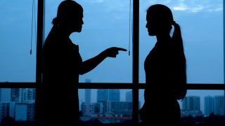 Silhouette of woman punishing her teenage daughter: generation conflict