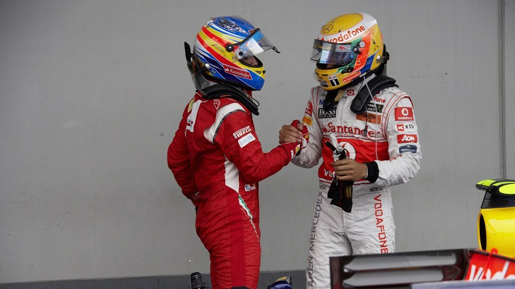 Second placed Fernando Alonso of Ferrari congratulates race winner Lewis Hamilton of McLaren, third placed Webber arrives in front, Germany, Nuerburgring, 24 July 2011. (Photo by Rainer W. Schlegelmilch/Getty Images)