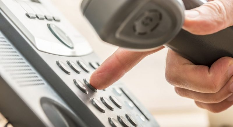 Closeup of male telemarketing salesperson holding a telephone receiver dialing phone number to make a business call.