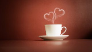 cup of tea with steam in two heart shape and dust on the base, vintage style, love concept