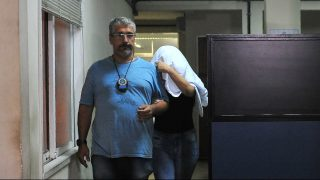 A Brazilian civil policeman escorts the wife of Greece's ambassador to Brazil Kyriakos Amiridis, Francoise de Souza Oliveira, who murdered him in a plot hatched with her police officer lover, who confessed to the crime, on December 30, 2016 in Rio de Janeiro.    Amiridis, 59, was killed on December 26 by the officer, Sergio Gomez Moreira, and his charred body was found on December 29 in his burned-out rental car, a day after his wife declared him missing.  / AFP PHOTO / Fabio Teixeira