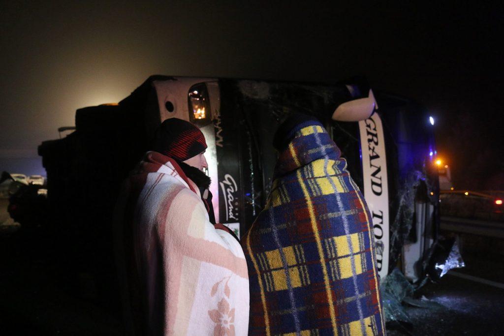 Miskolc, 2016. december 18. Pokrócba burkolódzó utasok felborult és összetört autóbusz mellett 2016. december 18-án kora hajnalban az M3-as autópályán a Miskolc felé vezetõ oldalon, a Mezõkeresztes és Mezõkövesd közötti részen, ahol az elsõdleges adatok szerint hárman meghaltak a buszbalesetben. A már felborult jármûnek több autó is nekirohant, ketten súlyosan, huszonhárman pedig könnyebben sérültek meg. MTI Fotó: Vajda János