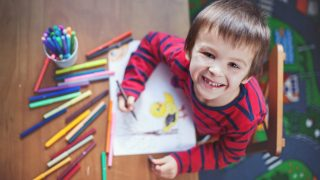 Adorable little boy, drawing picture for easter at home, having fun, smiling at camera, shot from above