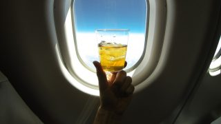 Refreshing glass of ice tea (or alcohol mix) centered on the window of a jumbo airplane, with blue sky above and snowy white clowds below.