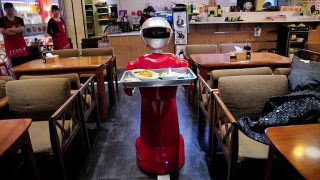 "SHENYANG, CHINA - MARCH 15:  (CHINA OUT) A robot delivers meals for customers at a restaurant on March 15, 2016 in Shenyang, Liaoning Province of China. The robot which's in 140 centimeters high and 60 kilograms weight can communicate daily words with customers like ""Hello"", ""Please"", ""See you again"" and so on. One robot will cost about 60,000 RMB yuan and could work for ten years with 8-hour working per day.  (Photo by VCG/VCG via Getty Images)"