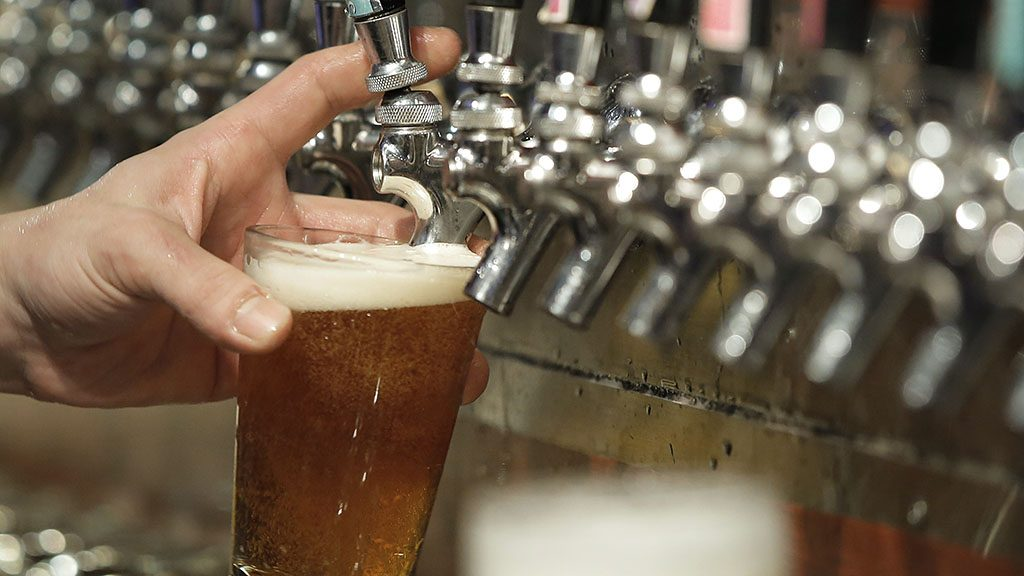 A bartender pours a glass of craft beer from a draft beer tap inside the Bakusyu Club Popeye bar in the Ryogoku neighborhood of Tokyo, Japan, on Friday, May 1, 2015. Craft beer is gaining popularity in Japan, much like it has in the U.S. and Europe. The four beverage giants -- Asahi Group Holdings Ltd., Kirin Holdings Co., Suntory Holdings Ltd. and Sapporo Holdings Ltd. -- are experimenting with alternative brews too as they face a slide in consumption. Photographer: Kiyoshi Ota/Bloomberg via Getty Images