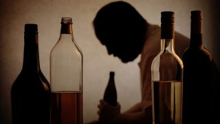 silhouette of a person drinking behind bottles of alcohol with added filter