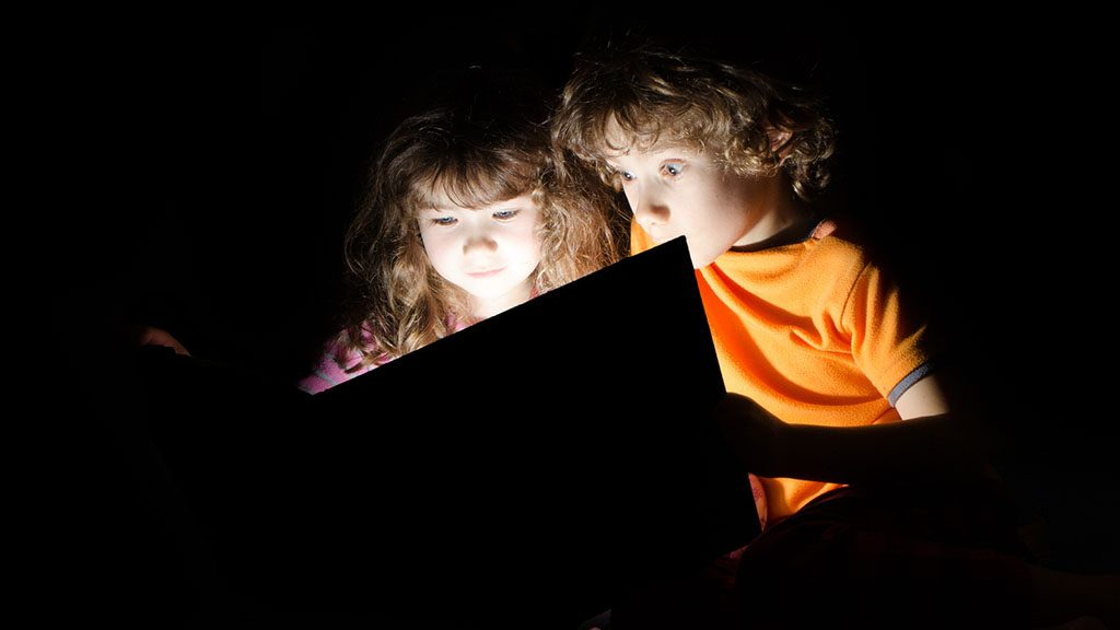 A boy and a girl reading a magic book and being lit by the book