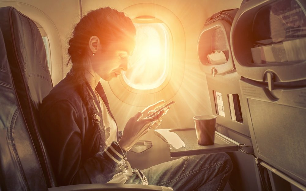 Woman sitting at airplane and looking to mobil phone.