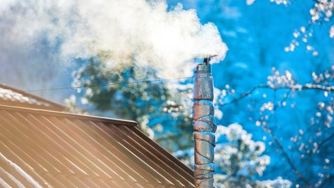 Smoke from the chimney on the roof at sunny day
