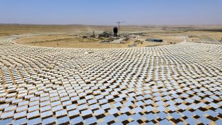 A picture taken on May 26, 2016, shows some of the 55,000 mirrors directing sunlight toward the Ashalim solar tower which is under construction near the southern Israeli kibbutz of Ashalim in the Negev desert. In the middle of the Israeli desert, engineers are at work building the world's highest solar tower, its peak set to resemble a giant lighthouse, beckoning toward the country's hopes in renewable energy. A field of mirrors expanding 300 hectares -- the size of more than 400 football pitches -- will stretch out at its base, directing sunlight toward the tower's peak to an area called the boiler, which resembles a huge lightbulb where electricity is produced. The construction, estimated at a cost of 500 million euros ($570 million), is being financed by US firm General Electric, with French company Alstom and Israeli private investment fund Noy also involved. The construction, estimated at a cost of 500 million euros ($570 million), is being financed by US firm General Electric, with French company Alstom and Israeli private investment fund Noy also involved. / AFP PHOTO / JACK GUEZ / TO GO WITH AFP STORY BY DAPHNE ROUSSEAU
