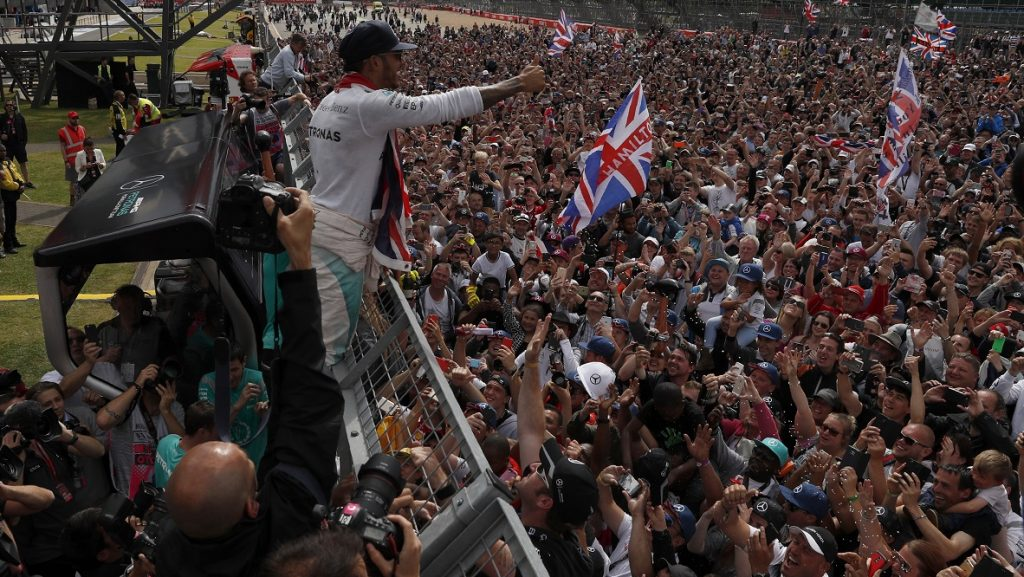 Mercedes AMG Petronas F1 Team's British driver Lewis Hamilton celebrates with the fans after winning the British Formula One Grand Prix at Silverstone motor racing circuit in Silverstone, central England, on July 10, 2016. Lewis Hamilton streaked away to comfortably win his home British Grand Prix on Sunday, with Mercedes team-mate Nico Rosberg hanging on for a provisional second. Third was the Red Bull of Max Verstappen, but championship leader Rosberg -- suffering late gear-box trouble -- was under investigation over a radio communication that could spell further trouble for the German.  / AFP PHOTO / ADRIAN DENNIS